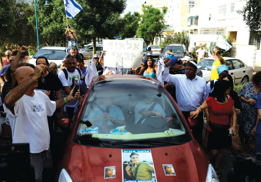 SUPPORTERS OF Elor Azaria cheer.