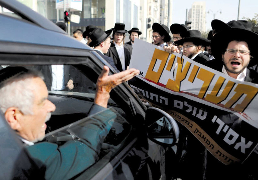 A DRIVER argues with haredi men as they protest against the detention of members of their community