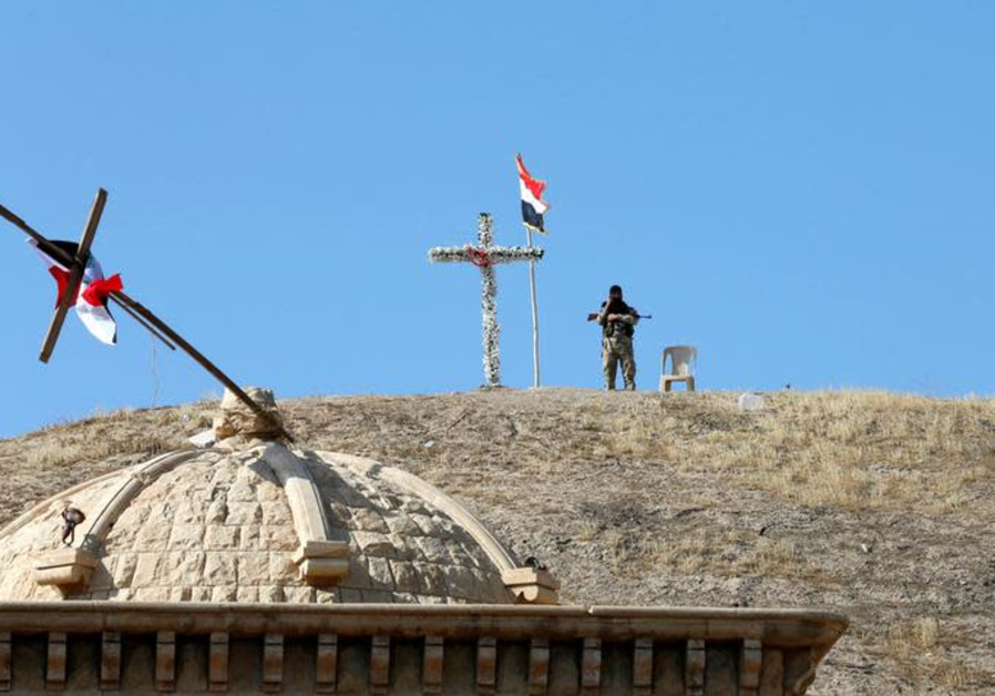 An Iraqi Christian soldier guards the church of Saint Barbara after it was recaptured from ISIS