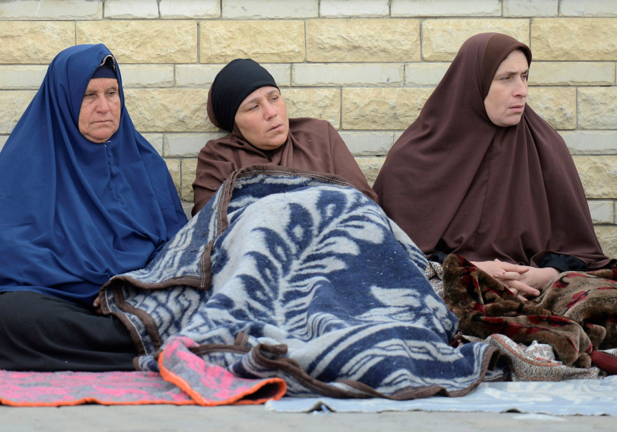 Relatives of victims of the explosion at Al-Rawda mosque, sit outside Suez Canal University hospital