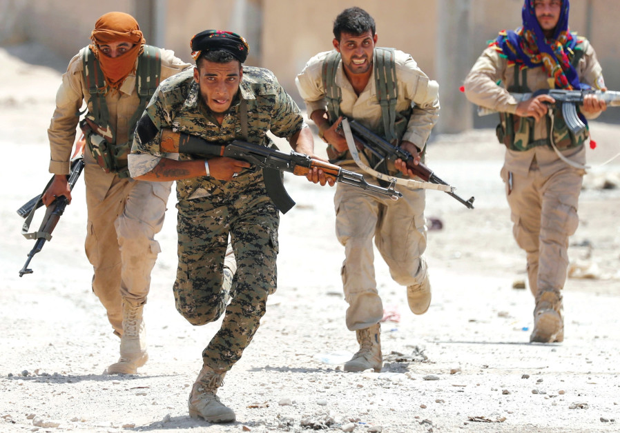 KURDISH FIGHTERS from the People's Protection Units (YPG) run across a street in Raqqa, Syria in Jul