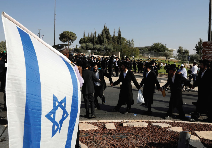 ULTRA-ORTHODOX JEWS dance as they protest outside the Knesset last month.