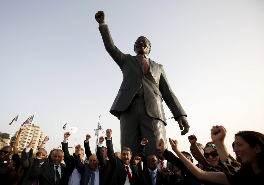 People cheer in front of a Nelson Mandela statue in Ramallah