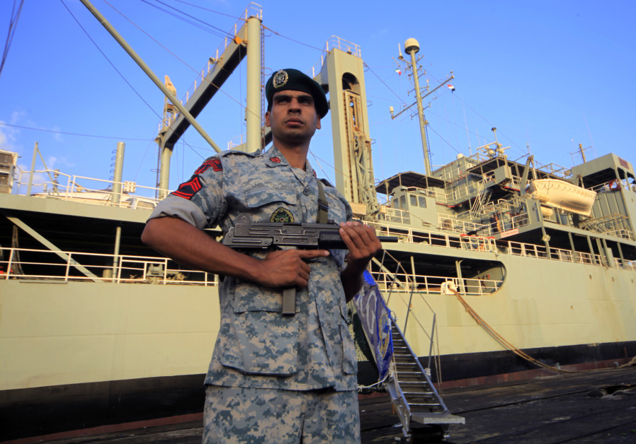 An Iranian soldier stands guard near Iranian Navy helicopter carrier