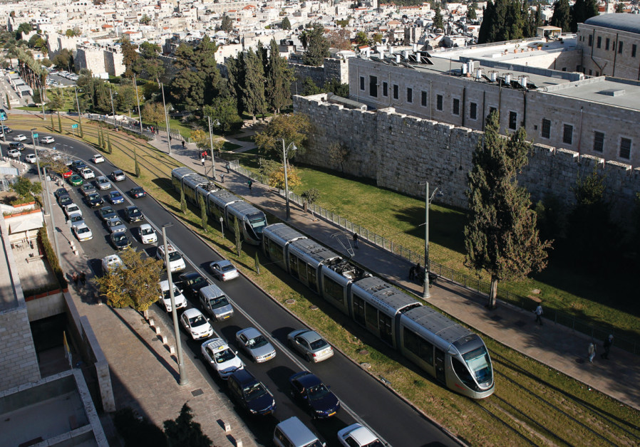 Cars come to a standstill as the light rail passes outside the walls of Jerusalem's Old City