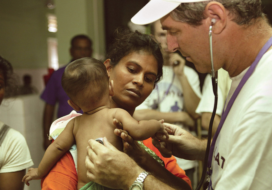 SHEBA MEDICA CENTER'S Prof. Eli Schwartz, a world specialist in tropical diseases, treats a child in