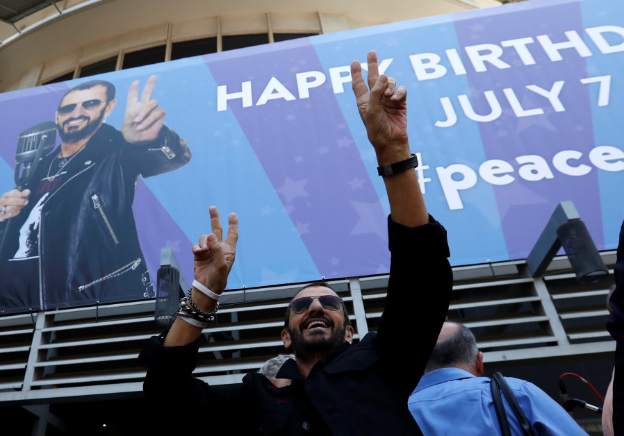 Musician Ringo Starr gestures at fans at a 'Peace & Love' event to celebrate Starr's 77th birthday i