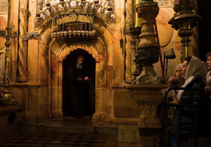 Worshippers stand nearby as a priest peers out from the Edicule, the burial place housing the purpor