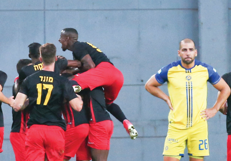 Maccabi Tel Aviv defender Tal Ben-Haim (right) looks on disappointed as Ashdod SC players celebrate