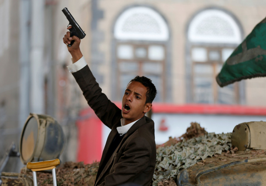 A Houthi militant reacts as he sits on a tank after the death of Yemen's former president Ali Abdull