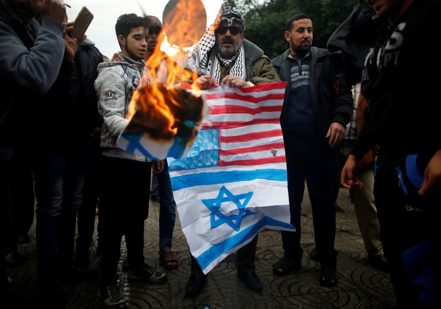 Palestinians burn signs depicting an Israeli flag and a U.S. flag during a protest against the U.S.