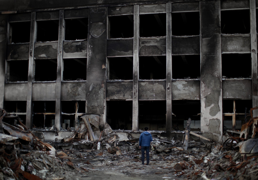 A man stands in front of a fully burned elementary school near the the crippled Fukushima nuclear po