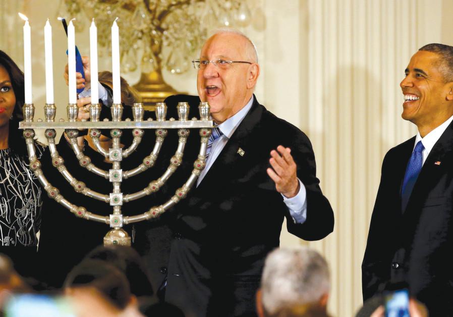 PRESIDENT Reuven Rivlin (center) lights a hanukkia as he joins former US president Barack Obama and