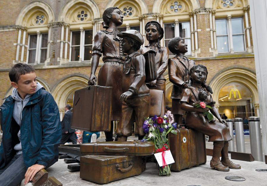 A TRAVELER looks toward the 'Kindertransport' memorial in London