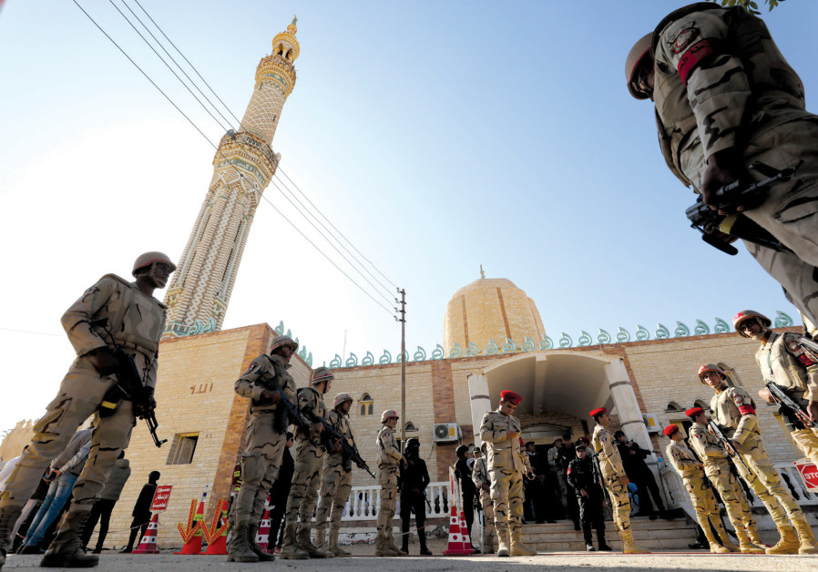 EGYPTIAN SOLDIERS watch over worshipers outside Al Rawdah mosque earlier this month after the deadly