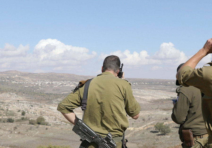 IDF soldiers look over a border fence between the Israeli side of the Golan Heights and Syria