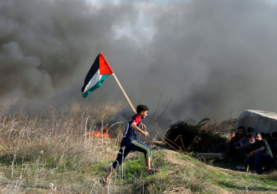 A protester holds a Palestinian flag as he runs during clashes with Israeli troops