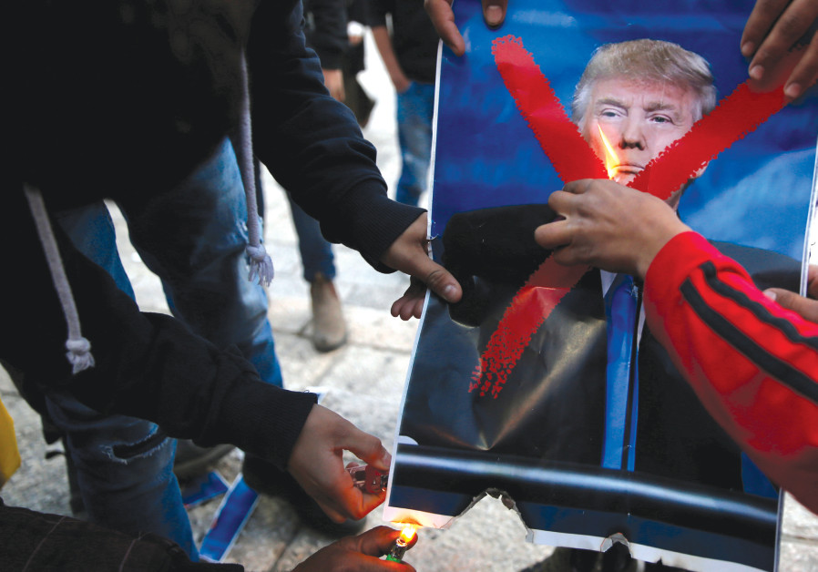 PALESTINIANS BURN a picture of US President Donald Trump as they take part in a protest against Trum