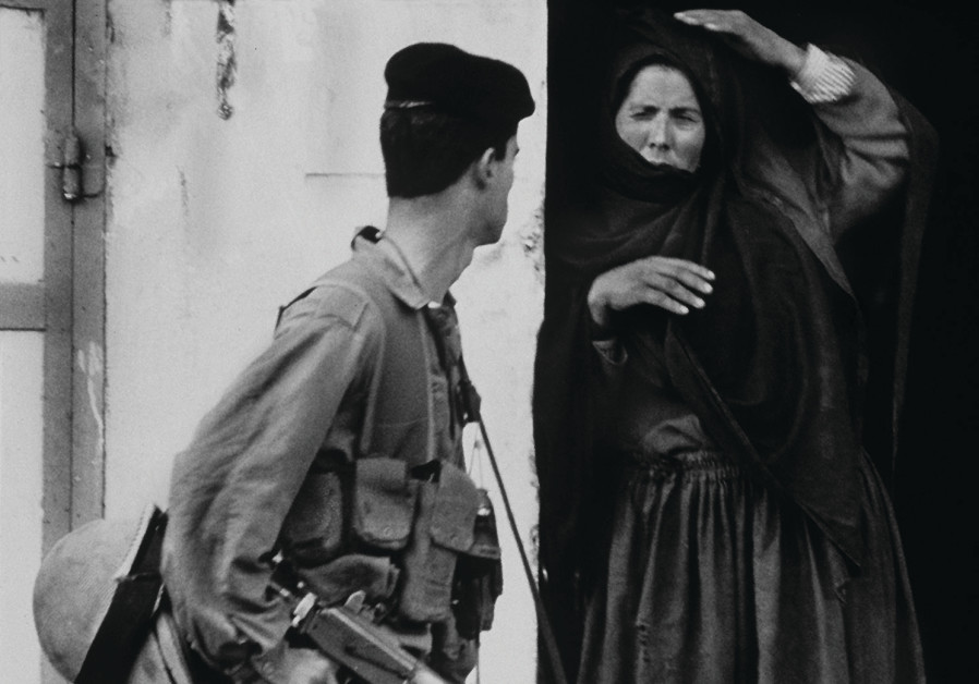 A PALESTINIAN woman and an Israeli soldier exchange glances as he passes her house in Rafah, at the