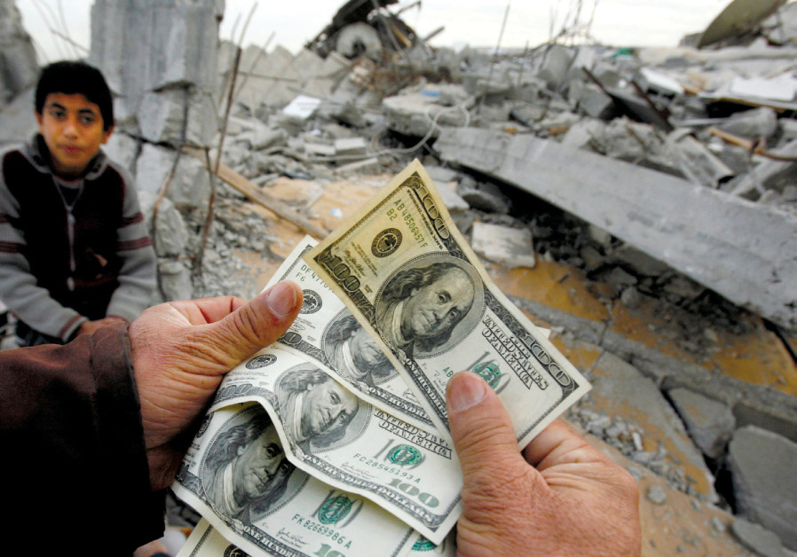 A PALESTINIAN whose house was destroyed by an Israeli air strike shows money distributed by Hamas in