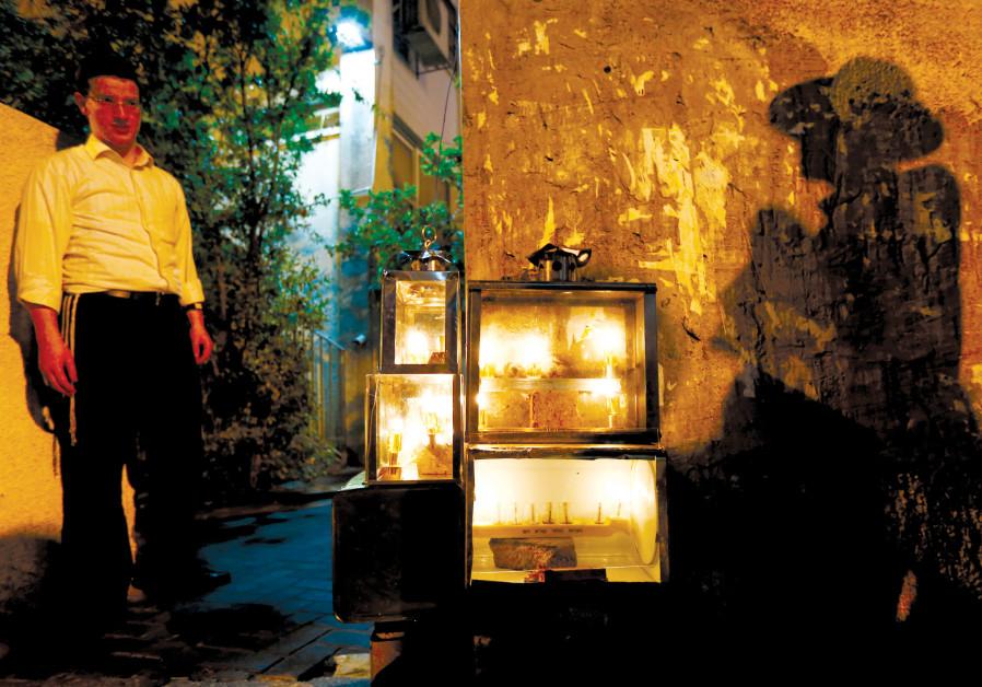 A MAN casts a shadow near candles lit for Hanukka in Ashdod