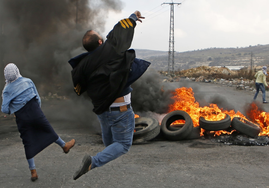 Palestinians throw stones at Israeli soldiers at a riot near Ramallah, December 2017