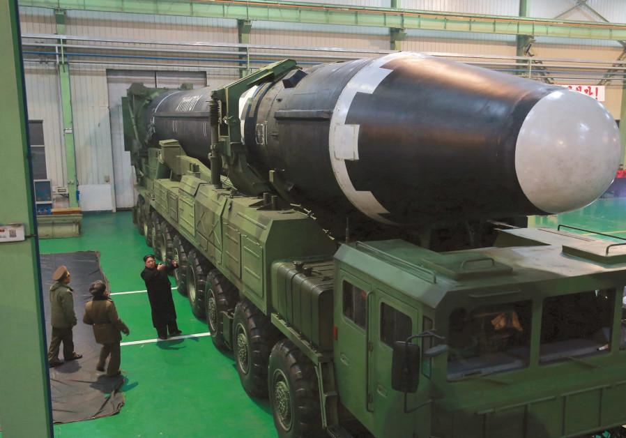 NORTH KOREA'S leader Kim Jong Un gestures beside the newly developed intercontinental ballistic rock