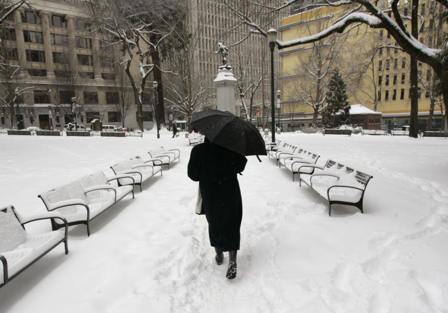 A pedestrian walks through a snow covered park in downtown Portland, Oregon.