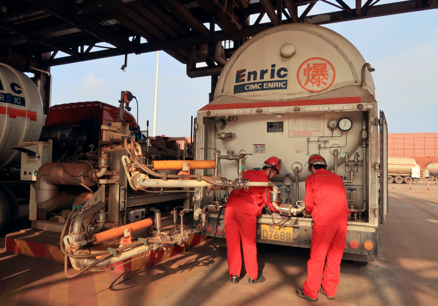 Workers get ready to pump liquefied natural gas into a gas trailer at CNPC Caofeidian terminal, in T