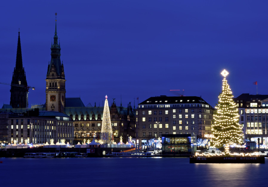 An illuminated Christmas tree shines in front of the Christmas market in Hamburg, Germany