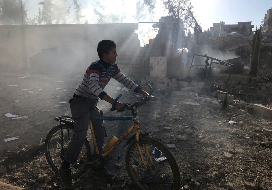A Palestinian boy near a militant target that was hit in an Israeli airstrike in Gaza