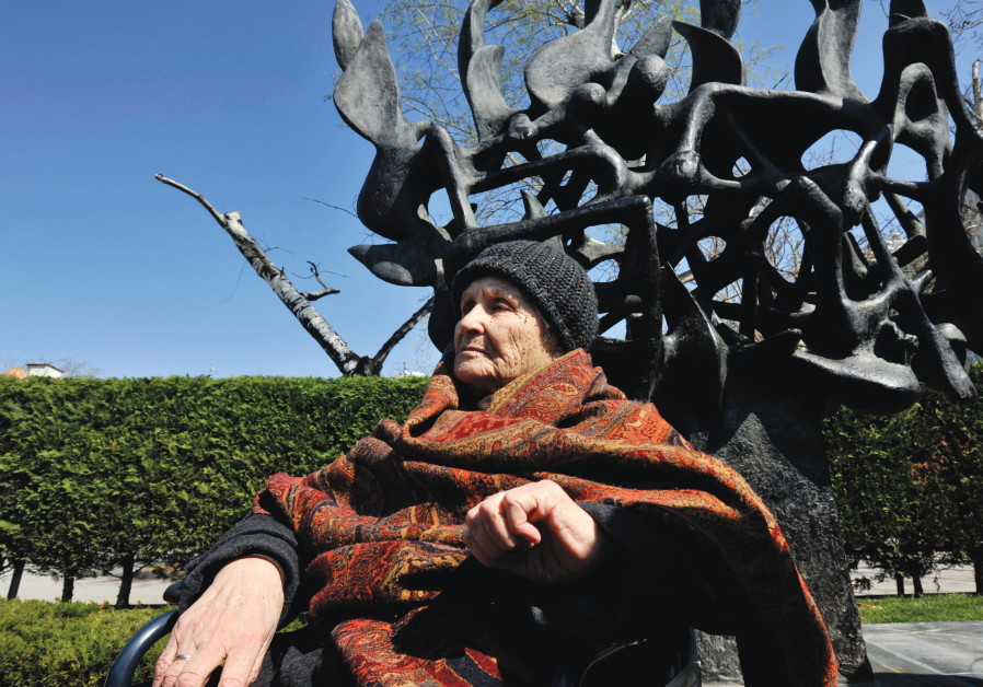 HOLOCAUST SURVIVOR Janna Saatsoglou sits in front of a Holocaust monument during the 70th anniversar