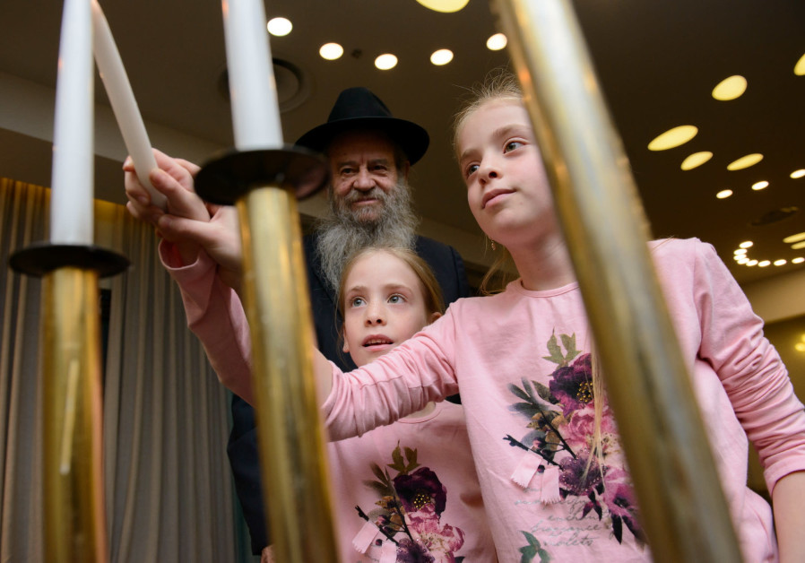Rabbi Amram Blau lights candles with children who have lost their fathers