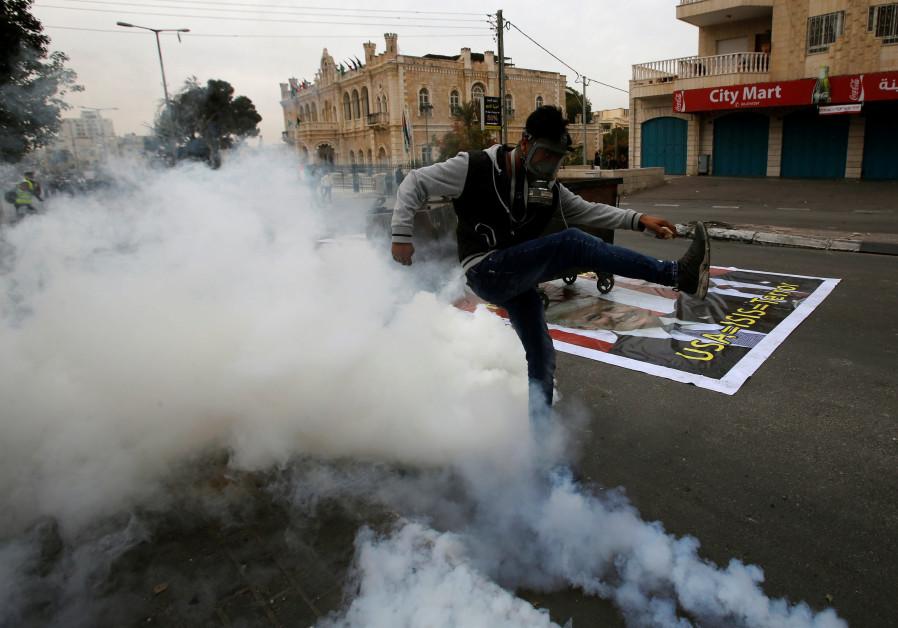 A Palestinian demonstrator kicks a tear gas canister fired by Israeli troops in Bethlehem