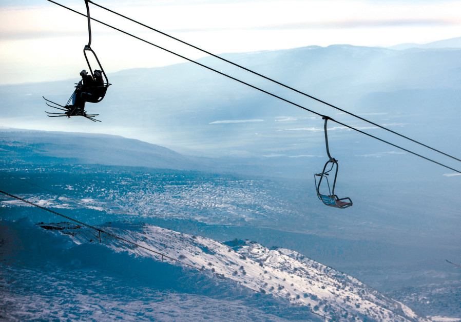SKIERS RIDE a ski lift on Mount Hermon in the Golan Heights
