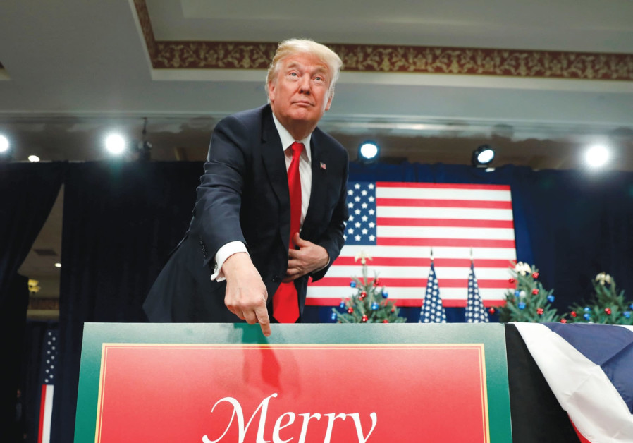 US PRESIDENT Donald Trump points at a Christmas sign.
