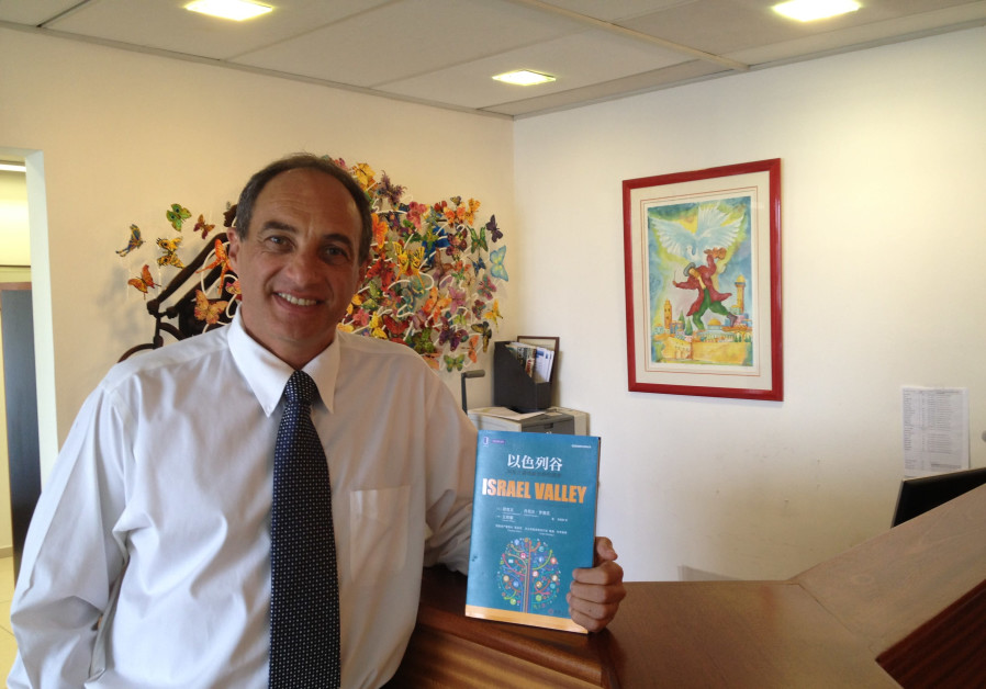 Israeli private equity investor Edouard Cukierman holds up a book he co-authored that was translated