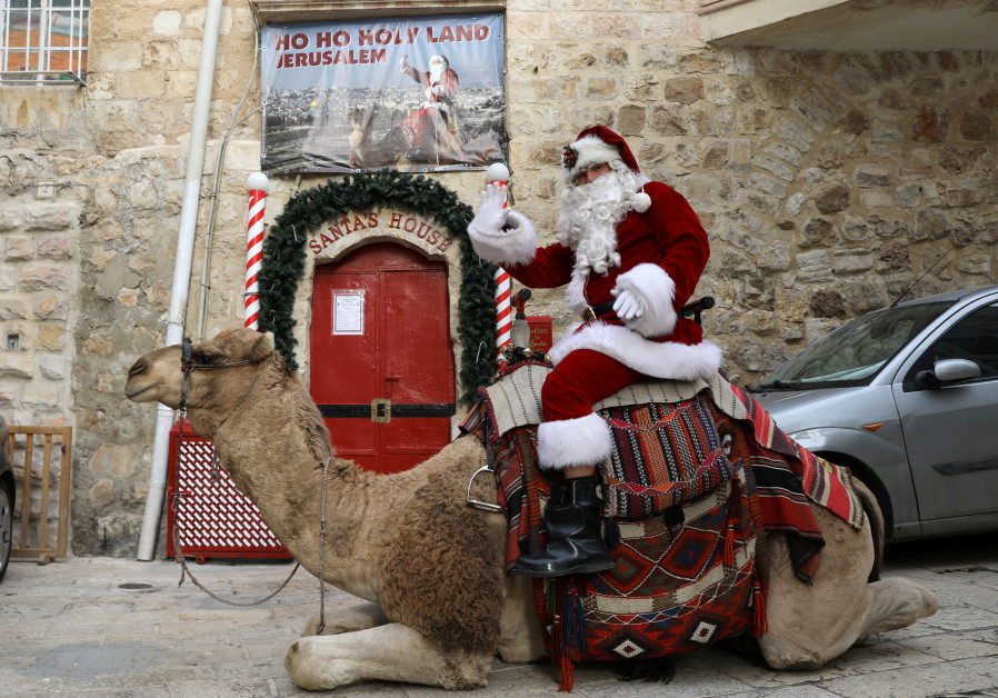 Issa Kassissieh, wearing a Santa Claus costume, rides a camel during the annual Christmas tree dist