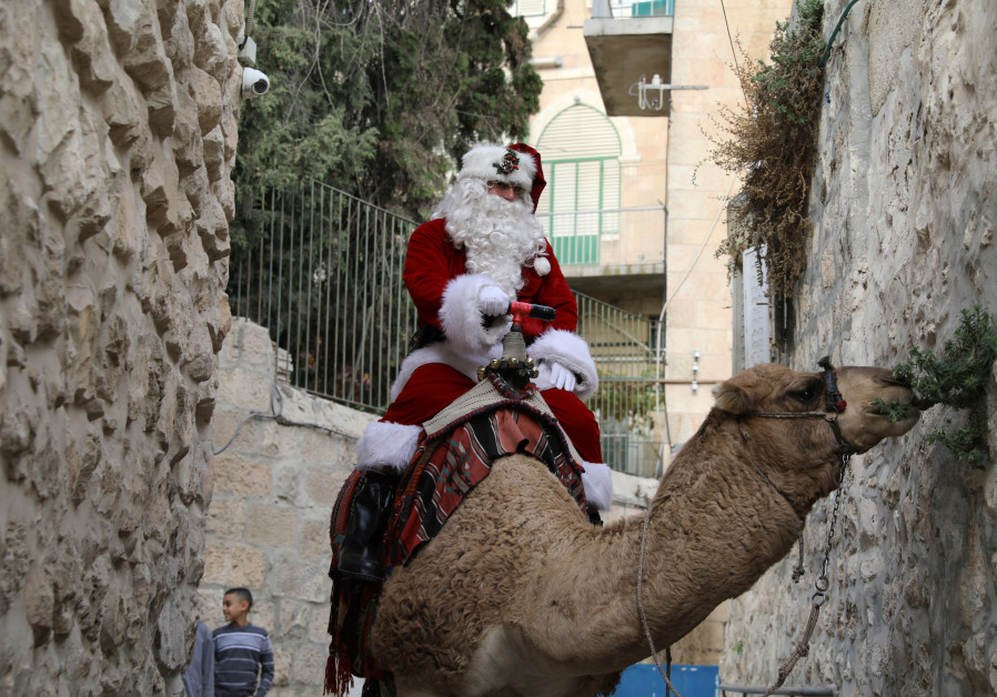 Issa Kassissieh, wearing a Santa Claus costume, rides a camel and distributes Christmas trees in Je