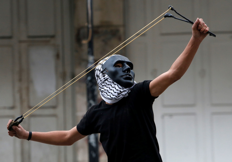 A Palestinian demonstrator uses a slingshot to hurl stones towards Israeli troops during clashes at