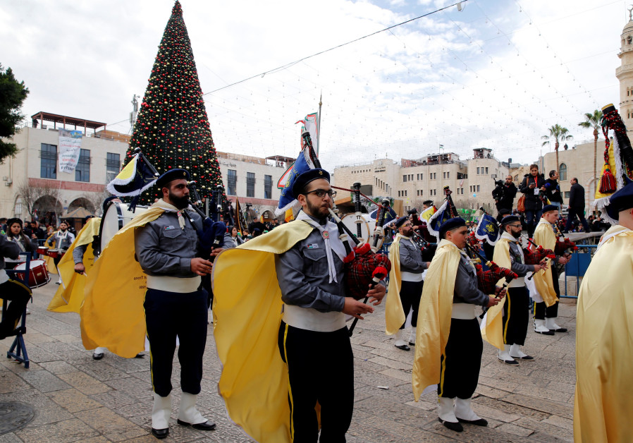 A Palestinian marching band takes part in a Christmas parade outside the Church of the Nativity in B
