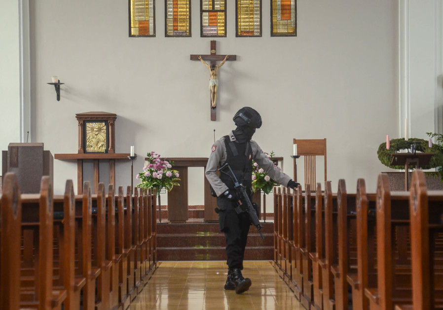 An Indonesian bomb squad policeman holds a rifle as he examines a church before Christmas mass praye