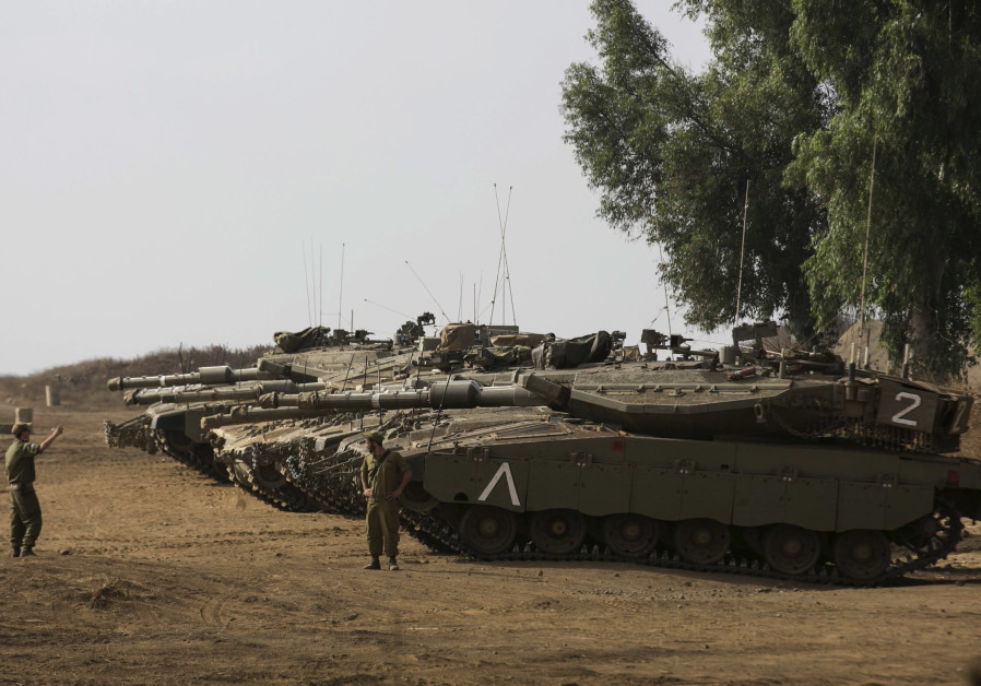 An Israeli soldier directs a tank during an exercise in the Golan Heights.