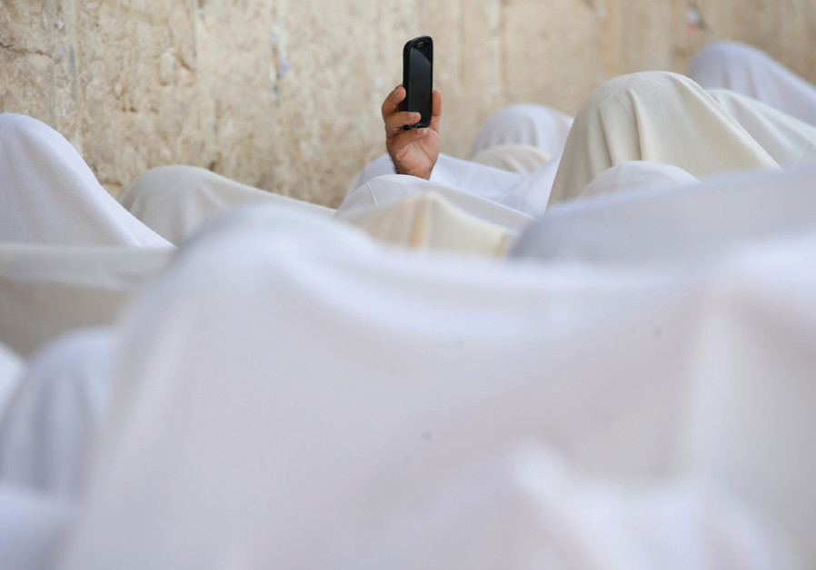 A man holds up a cellphone during the priestly blessing at the Western Wall