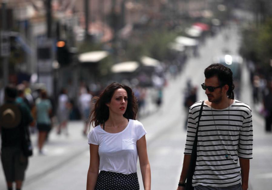 A young couple walk down Jerusalem's Jaffa Road