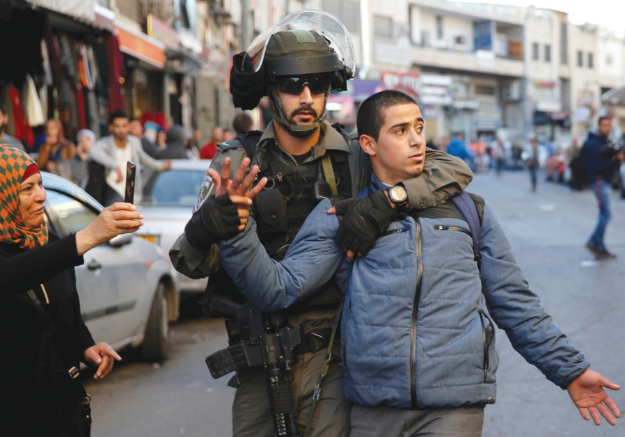 An Israeli border police officer detains a Palestinian protester  demonstration in east Jerusalem