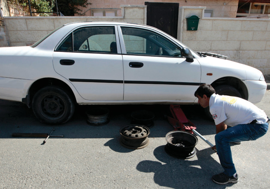 A man changes the tire on a car in Abu Ghosh, near Jerusalem