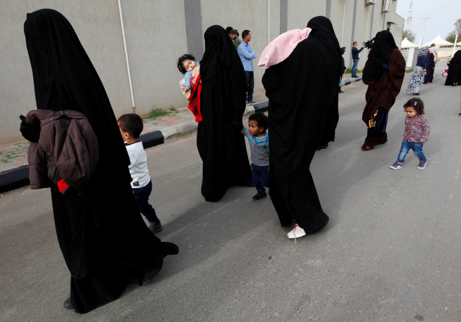 Female jihadists walk with their children at Reform and Rehabilitation foundation in Mitiga in Tripo