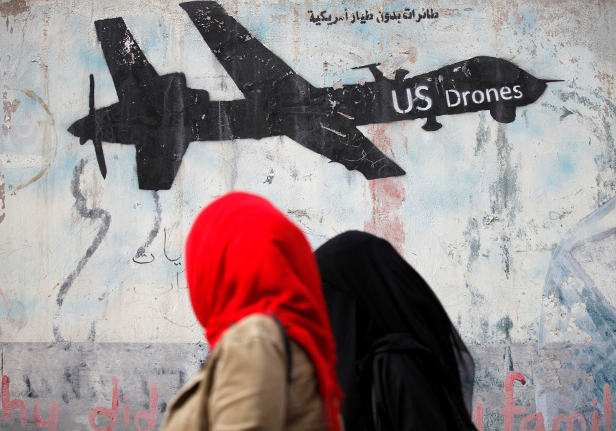 Women walk past a graffiti, denouncing strikes by US drones in Yemen, painted on a wall in Sanaa,