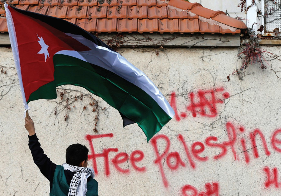 A BOY holds the Jordanian national flag during a protest near the US Embassy in Amman, Jordan.